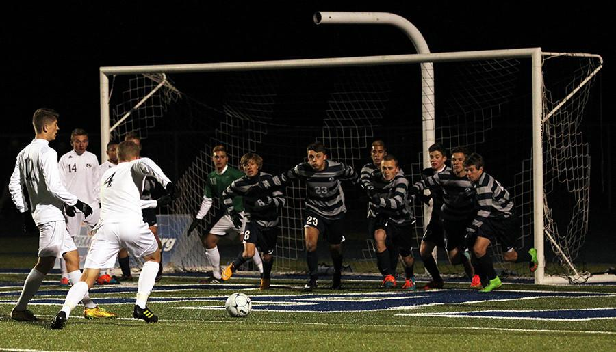 Sprinting toward Lee's Summit's Dalton Souder, eight members of the boys soccer team concentrate on blocking his shot on goal during the Spartans 2-1 loss to the Tigers in the state semifinals. The team braved below freezing temperatures in Kansas City and wound up claiming third place — the school's first state soccer trophy — and posting the best record in school history. PHOTO BY JERIANNE HARRISON